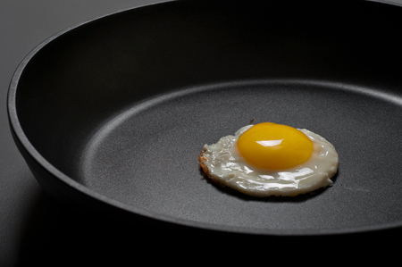 nonstick: Fried eggs in the new black non-stick frying pan close-up.