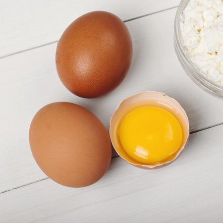 huevo blanco: Todo y rotos huevos marrones sin procesar en blanco primer de madera de la mesa.