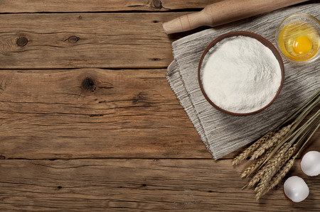 Flour in a bowl with ingredients for preparing baked products. Top view. Standard-Bild