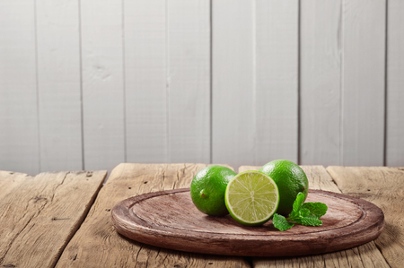 rustic kitchen: Fresh limes with mint leaves on wooden background on rustic kitchen.