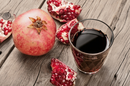 pomegranate: Glass of pomegranate juice with slices of pomegranate and whole pomegranate close up on wooden surface. Stock Photo