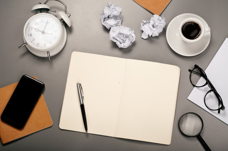 pen and paper: Open notebook with blank pages with a pen, glasses, coffee cup, mobile phone, alarm clock and crumpled paper on a grey desktop. Stock Photo