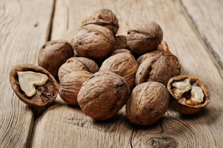 surface closeup: Handful walnuts on the wooden surface closeup. Stock Photo
