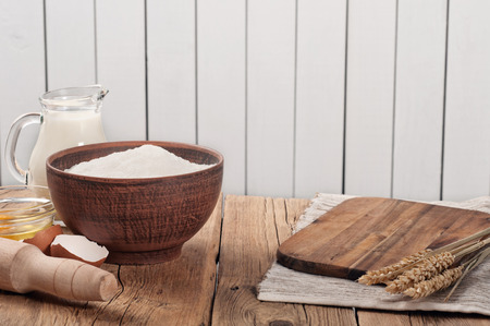 rustic kitchen: Flour in a clay bowl on a rustic kitchen table with rolling pin, ears of wheat, milk and eggs.