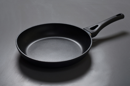 nonstick: New black frying pan with non-stick coating on a gray surface closeup. Top view