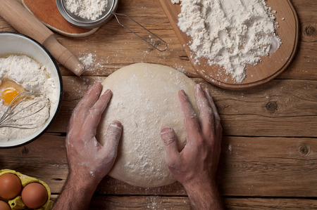 knead: Male baker prepares bread on a wooden table in a bakery closeup. Top view. Stock Photo