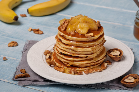 whole pecans: Pancakes with caramelized banana, nuts and honey on wooden table closeup. Top view with copy space