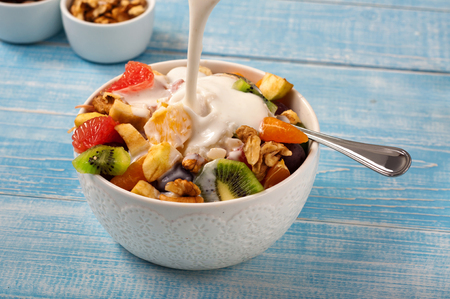 Fruit salad with yogurt and nuts closeup. Yogurt pouring in a fruit salad. Top view with copy space