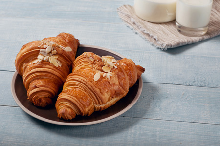 croissant: Fresh homemade croissants with almond chips on a wooden table in the rustic kitchen. Top view with copy space