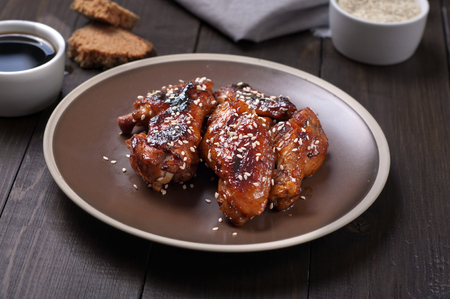 Chicken wings in a sweet and sour sauce with sesame seeds on a plate closeup on a wooden table Standard-Bild