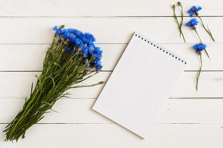 白い木製のテーブルの上のノートのためのノートと青い野生の花の美しい花束