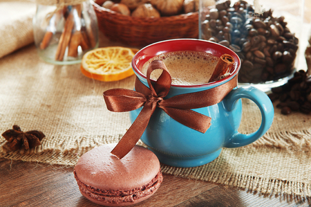 small cake: A cup of coffee costs on a wooden table. About cups worth of the bank with coffee beans and lie small cake macaron.