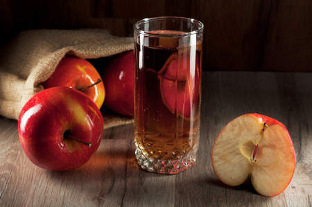 apple sack: fresh apple juice in a glass standing on a wooden table. Near the glass beaker, a sack of apples