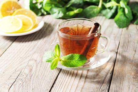 hojas secas: Té negro en una taza y un plato de vidrio y hojas de menta en una mesa de madera