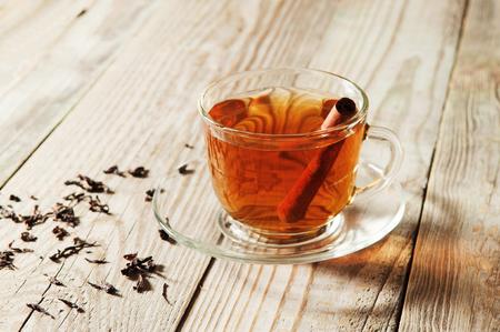 Glas Tasse und Untertasse schwarzer Tee mit Zimt steht auf einem Holztisch.