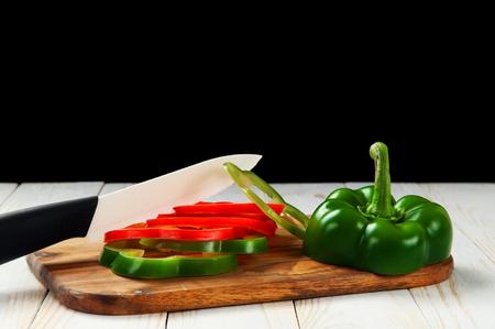 cuchillo de cocina: Los pimientos dulces de dos colores, rojo y verde, en rodajas en la tabla de cocina en una tabla de madera. Junto a la pimienta, cuchillo de cerámica blanca. Fondo negro. espacio de la copia