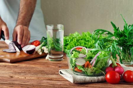 Ensalada fresca de verduras de verano en un recipiente hondo de cristal. Rúcula, lechuga, rábanos, cebollas, tomates cherry. En el fondo de la mano masculina en rodajas las cebollas en la tabla de cortar.