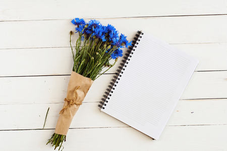 mazzo di fiori: bel mazzo di fiori di campo blu con un memo pad vuoto per le note su un tavolo di legno bianco