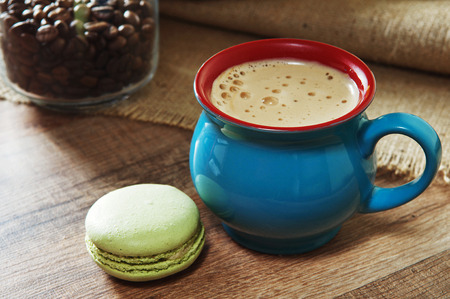 small cake: Coffee in beautiful cup standing on a wooden table. Next to a cup of coffee is a small cake macaron