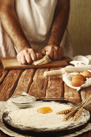 A handful of flour with egg yolk and wheat spikelets on the wooden desk. Against the background of men hands knead the dough. Ingredients for cooking flour products (bread, muffins, pie, pizza dough) Standard-Bild