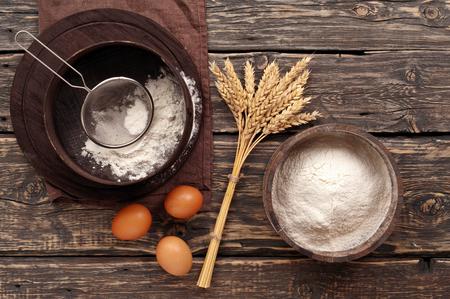 小麦、卵、暗いの素朴な木製背景、上面にふるいの耳を持つ木製のボウルに小麦粉パウダー 写真素材