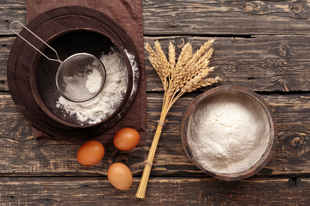 flour powder in a wooden bowl with ears of wheat, eggs and sieve on a dark rustic wooden background, top view