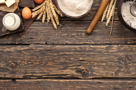 flour in a wooden bowl on dark wooden background with spikelets of wheat, eggs, milk and butter, top view with copy space. ingredients for bakery products