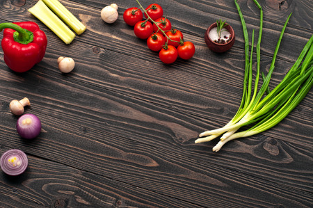 objec: Food background. On a dark wooden surface, cherry tomatoes, green onions, bulb onion, mushrooms and peppers. Top view with space for text or objec