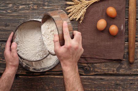 sift: baker sift the flour to make bread on a wooden dark surface, top view