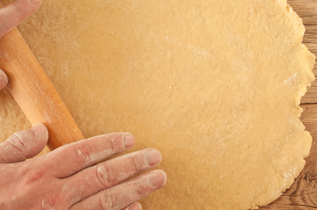 free backgrounds: baker rolls out the doughon a light wooden surface. Sunlight. Copy space Stock Photo