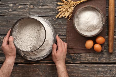 panadero: panadero Tamizar la harina sobre un fondo de madera rústica oscura en una panadería. Vista superior con espacio de copia