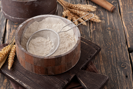 Flour in a wooden bowl with sieve on vintage board on a dark old table, closeup. Top view with copy space Foto de archivo