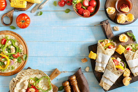 Tortilla with grilled chicken fillet and different vegetables on blue wooden table with copy space. Top view. Outdoors Food Concept Stock Photo