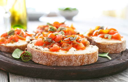 Sandwich with tomatoes, goat cheese and basil closeup. Delicious appetizer for wine Stock Photo