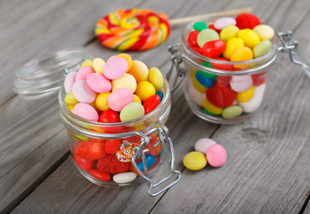 angled view: Two glass jars of colorful candy on a wooden table close up with copy space