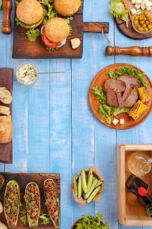 様々 な食品、グリルのハンバーガー、ステーキ、ぬいぐるみズッキーニ、野菜と青い木製のテーブル ソースのあるフレーム。 写真素材