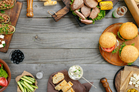 Frame with various foods, grilled burgers, steaks, stuffed zucchini, vegetables and sauces on a rustic wooden table. Outdoors Food Concept. Food background Stock Photo