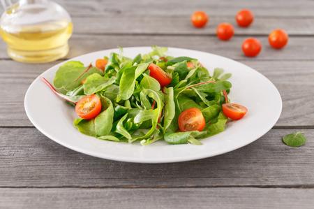 Ensalada italiana fresca en un plato blanco sobre una mesa de madera. Foto de archivo
