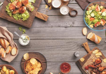 アウトドア料理のコンセプトです。コピー スペースを木製のテーブル別食品の焼き鶏の足、バッファローの翼、パン、サラダ、ジャガイモ、ポテト