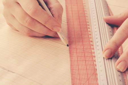 needlewoman: Close up hand fashion designer develops a sketch of the dress