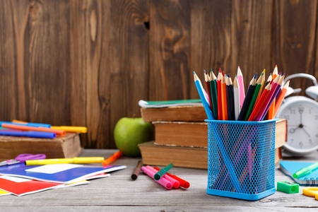 Colour pencils and school supplies on wooden desk with copy space