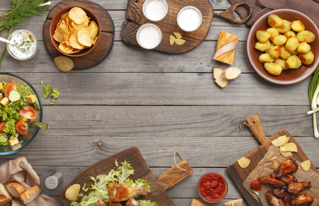 view to outside: Different food cooked on the grill on a wooden table with copy space, grilled chicken legs, buffalo wings, salad, potatoes, beer and snack to beer. Outdoors Food Concept Stock Photo