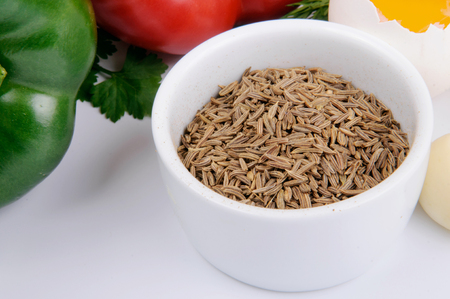 produits alimentaires: Graines de cumin dans un bol blanc avec des légumes sur fond blanc.