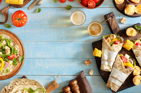 Tortilla with grilled chicken fillet, beer and vegetables on a blue wooden table with copy space. Top view. Stockfoto