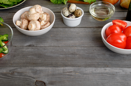 kitchen countertops: Kitchen wooden table with ingredients for cooking healthy and tasty food with copy space. Mushrooms, tomatoes, quail eggs, pepper, cucumber and olive oil on wooden table