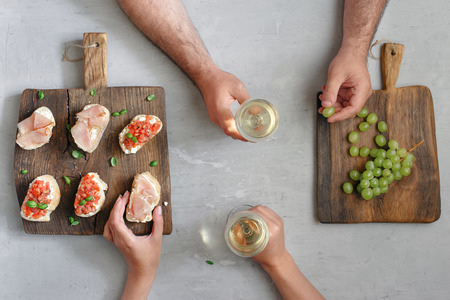 bacon love: Couple drinking wine with snacks for wine and grapes, top view