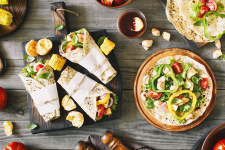 Roll tortilla with grilled chicken fillet on a wooden cutting board on a rustic wooden table with grilled vegetables, Top view. Фото со стока