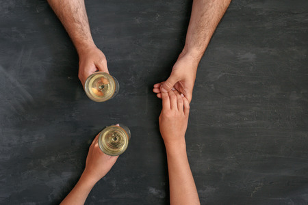 alcohol drinks: loving couple holding hands and drinking wine, top view