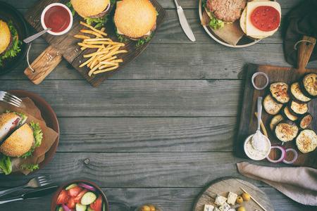 Capítulo de los distintos alimentos, hamburguesas, ensalada, queso roquefort y verduras cocinadas a la parrilla, vista desde arriba. Concepto de alimentos al aire libre