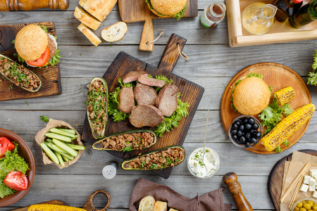 Steak grilled with different food, burgers, stuffed zucchini, vegetables, snacks and sauce on a wooden table, top view. Outdoors Food Concept. Food background